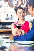Asian couple having dinner and drinking red wine in very fancy restaurant with open kitchen in backg