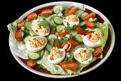 image of cucumber slice  - Closeup view of a salad of deviled eggs served with lettuce - JPG
