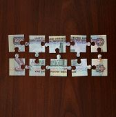 pic of dirhams  - UAE One Thousand Dirham note cut into jigsaw puzzle pieces - JPG