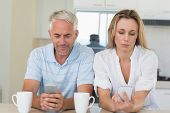 picture of not talking  - Distant couple sitting at the counter texting and not talking at home in the kitchen - JPG