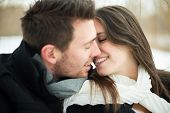 stock photo of blanket snow  - Attractive heterosexual couple kissing on a blanket in the snow - JPG