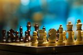 stock photo of chessboard  - Chess pieces on board on bright background  - JPG
