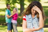 stock photo of breakup  - Portrait of an angry woman with man and girlfriend in background at the park - JPG