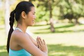 foto of namaste  - Side view of a sporty young woman in Namaste position at the park - JPG