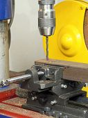 Stationary drilling machine with attached drill bit drilling a hole in metal structural