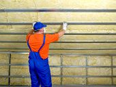 foto of insulator  - Construction worker thermally insulating house attic with mineral wool - JPG