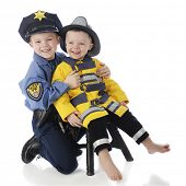 Little brothers posing together, the little one dressed as a fireman, the older his big brother dres