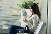 image of boredom  - young woman reading brochure in doctor - JPG