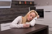 picture of sleepy  - Sleepy woman in modern kitchen with coffee - JPG
