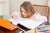 Cute little girl colouring at the table at home in kitchen