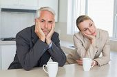 picture of boring  - Bored business couple having coffee before work in morning at home in the kitchen - JPG