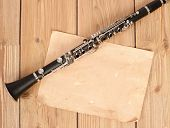 stock photo of clarinet  - clarinet and blank paper in wood background - JPG