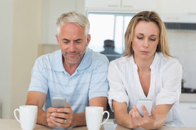 stock photo of not talking  - Distant couple sitting at the counter texting and not talking at home in the kitchen - JPG
