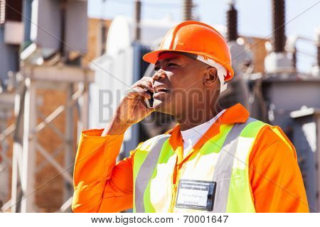 african electrical engineer using cell phone in substation