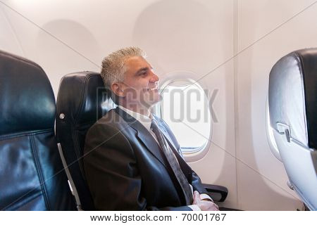 happy middle aged airplane passenger relaxing during flight on air plane