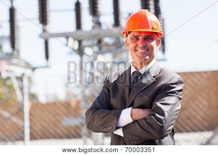 senior male industrial engineer in electricity substation with arms crossed