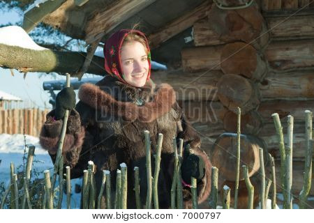 Girl Against Wooden House In Winter