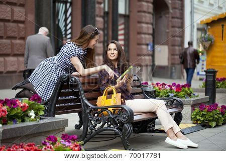 Two young girl friends sitting on a bench in the town center