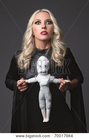 Witch holding a voodoo doll. Costume for Halloween Party. Blond witch.