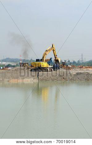 Excavator machine at edge of lake
