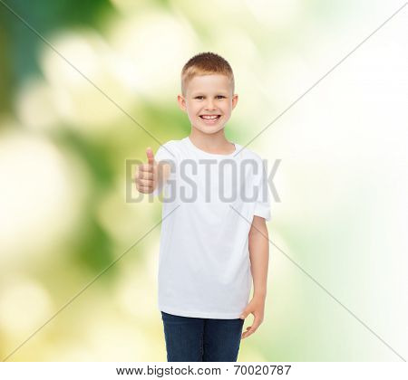 advertising, ecology, gesture, people and childhood concept - smiling boy in white blank t-shirt showing thumbs up over green background