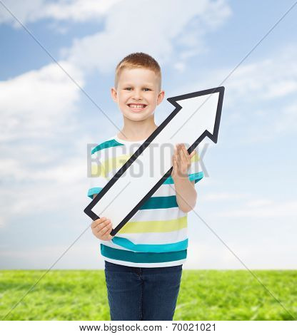 advertising, direction, environment and childhood concept - smiling little boy with white blank arrow pointing right over natural background