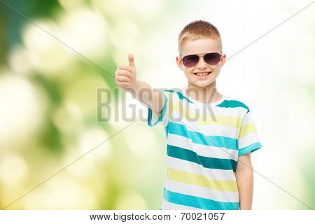 happiness, summer, childhood, gesture and people concept - smiling cute little boy in sunglasses over green background showing thumbs up