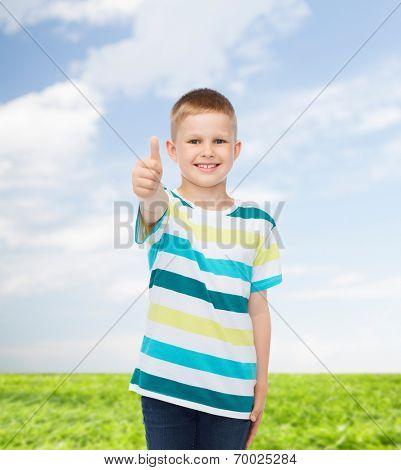 happiness, childhood, environment and people concept - smiling little boy in casual clothes showing thumbs up over natural background