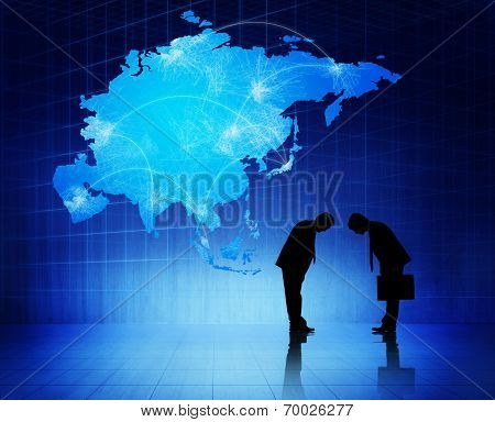 Two silhouettes of businessmen with blue cartography of Asia as a background.