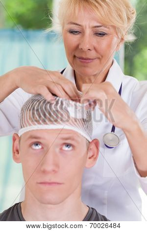 Doctor Applying Dressing After Head Injury