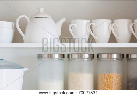 opened cupboard with kitchenware inside