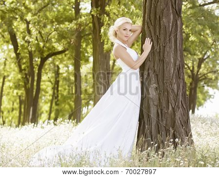 Portrait of beautiful bride in white dress in summer garden