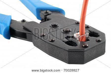 Crimping tool with a network cable isolated on white background.