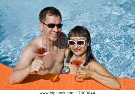 A Couple Holding Cocktail in a Pool