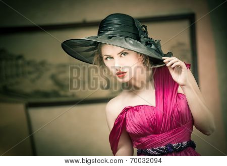 Charming blonde woman with black hat, retro image. Young beautiful fair hair female posing vintage.
