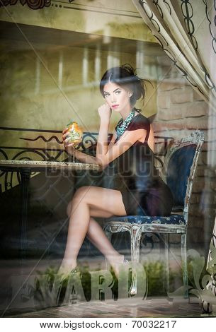 Fashionable attractive young woman in black dress sitting in restaurant, beyond the window