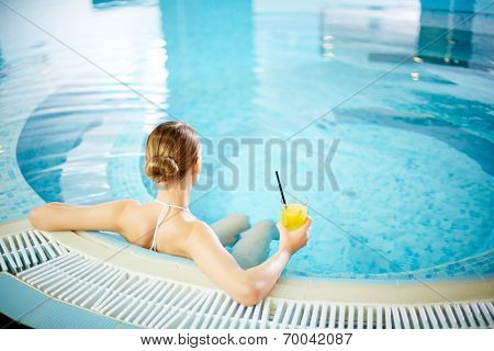 Young woman sitting in swimming pool with lemonade