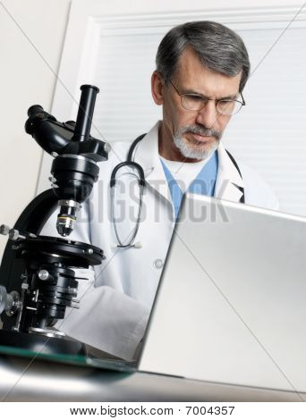 Doctor Analyzing Data At Laptop Computer And Microscope