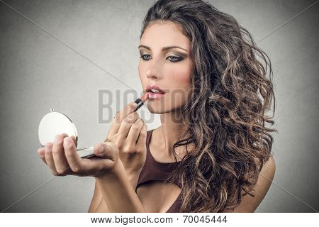 beautiful woman putting on her makeup