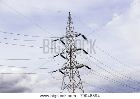 a high voltage transmission line tower against a light blue cloudy sky