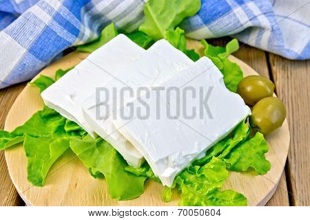 Feta With Olives And Lettuce On Board With Blue Cloth