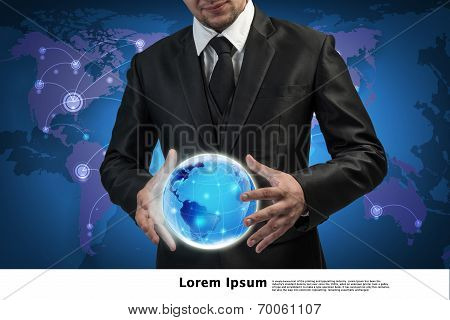 Business Man Holding The Small World In His Hands Against World Map Background