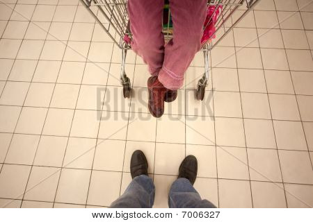 Top view on feet of little girl sitting in shoppingcart and her father standing opposite