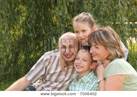 cheerful family with two children in early fall park. father mother little boy and girl is sitting n
