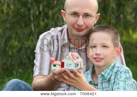 father and son keeping in their hands wendy house and looking at camera.