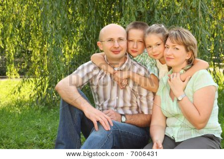 family with two children sitting at the grass near osier and looking at camera