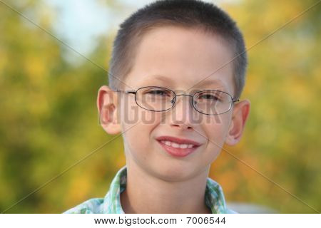 portrait of little boy in early fall park. he is looking at camera and smiling