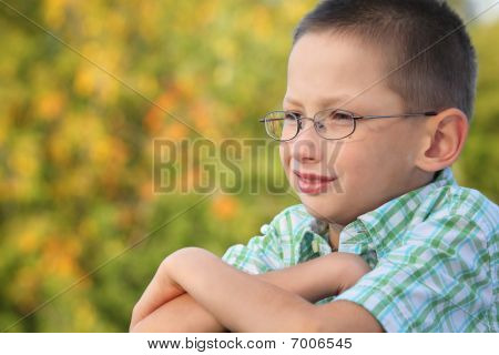 portrait of little boy with arms across in early fall park. he is looking away