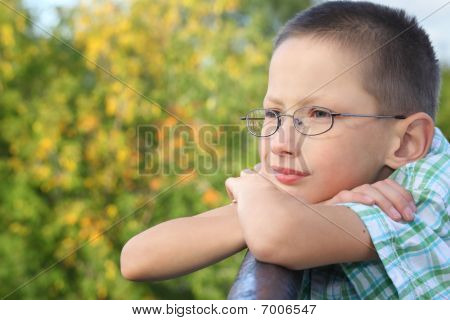 little boy is lean elbow on bridge fence and looking forward