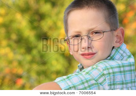 portrait of little boy in early fall park. he is looking at camera.